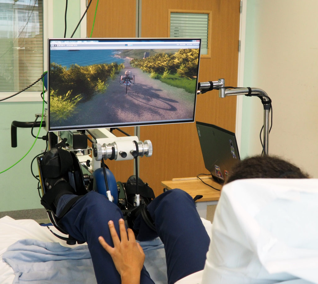 A nurse at Birmingham's Queen Elizabeth Hospital evaluating a novel rehabilitation programme, using a MOTOMed® supine exercise device to control a simulated recumbent trike along a virtual recreation of part of the south west coastal path